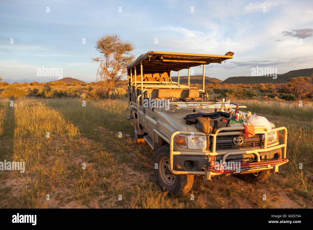 Etosha National Park Namibia Sunset on tourist Toyota Landcruiser with wine and other refreshments on the hood , - Stock Image