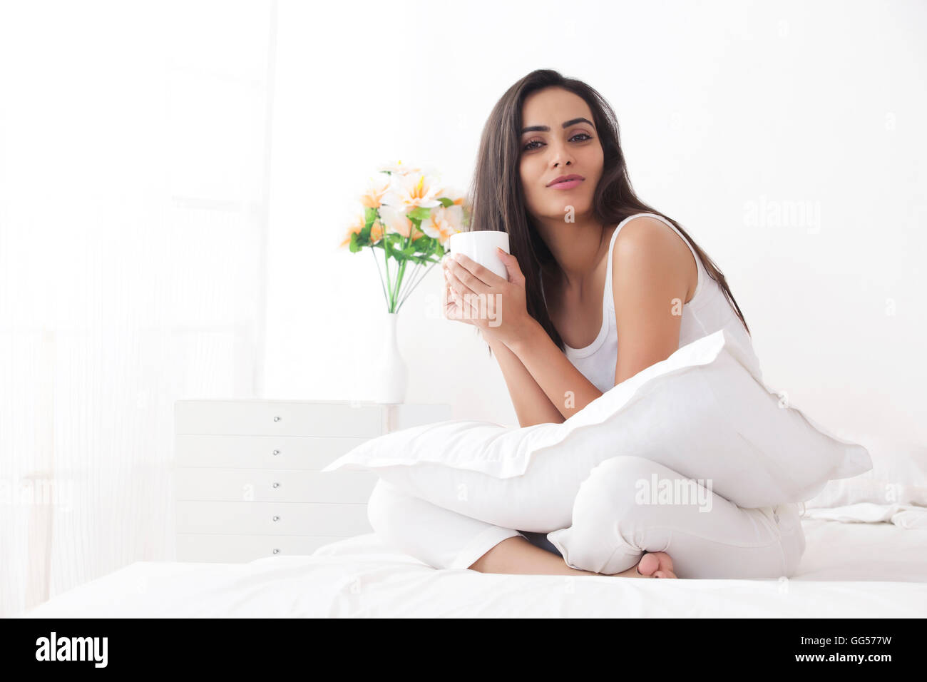 Portrait of beautiful young woman in nightwear holding coffee cup on bed - Stock Image