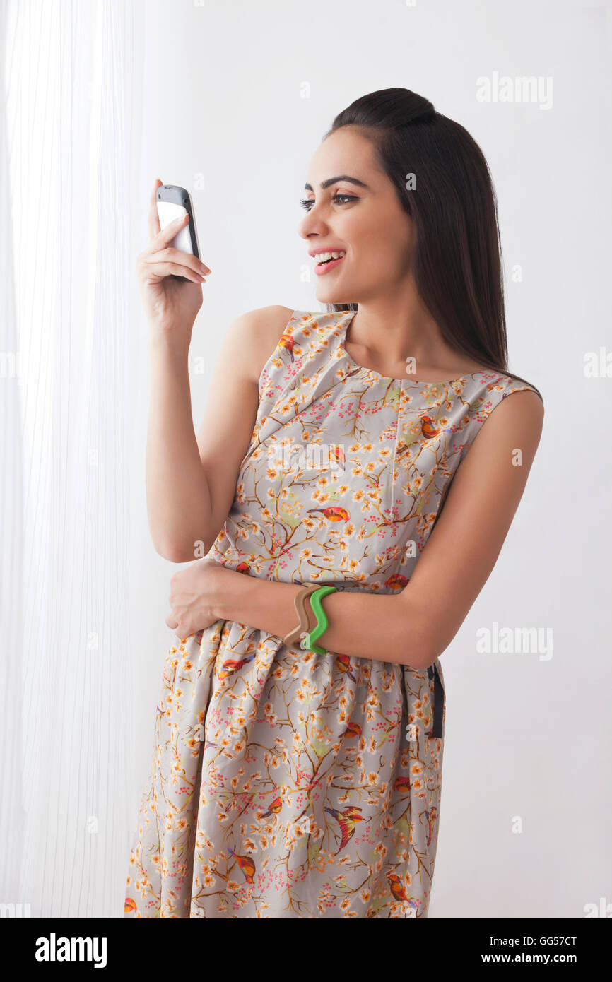 Happy young woman in sundress using cell phone by curtains Stock Photo
