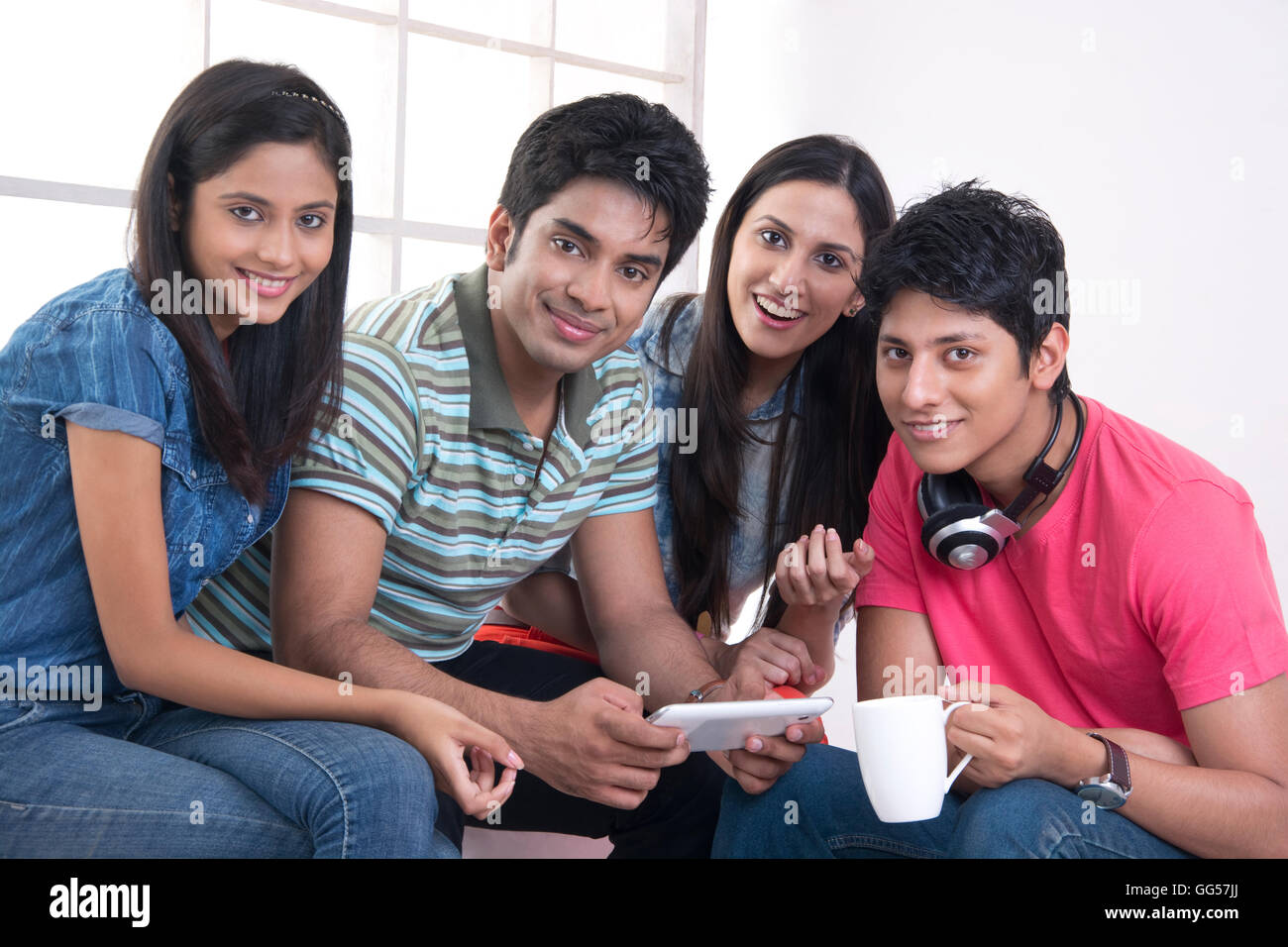 Portrait of happy friends spending leisure time in college - Stock Image