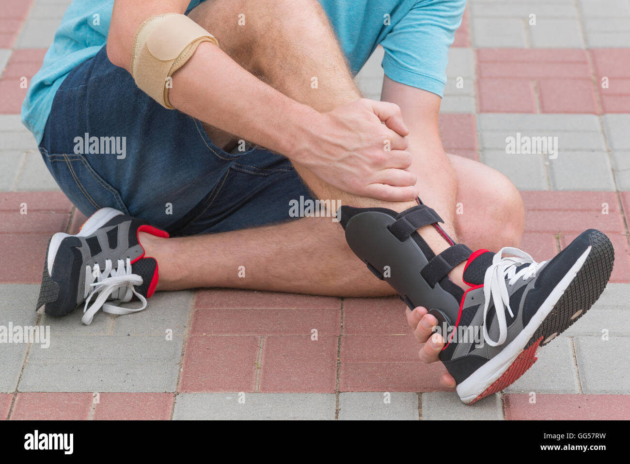 Man in athletic sneakers sitting on the street and checking his ankle orthosis or brace - Stock Image