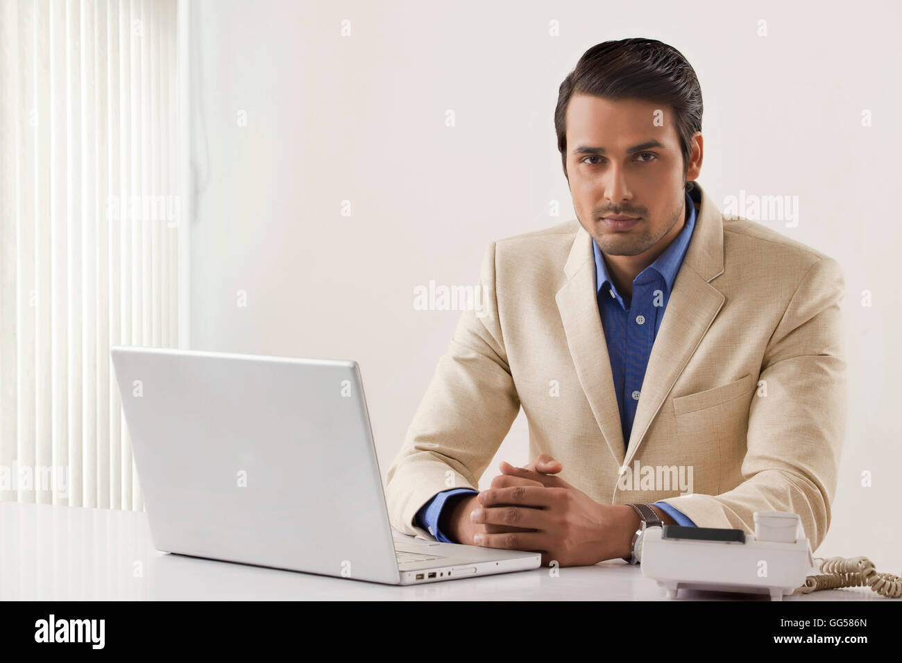 Portrait of confident businessman with laptop and landline at office desk - Stock Image