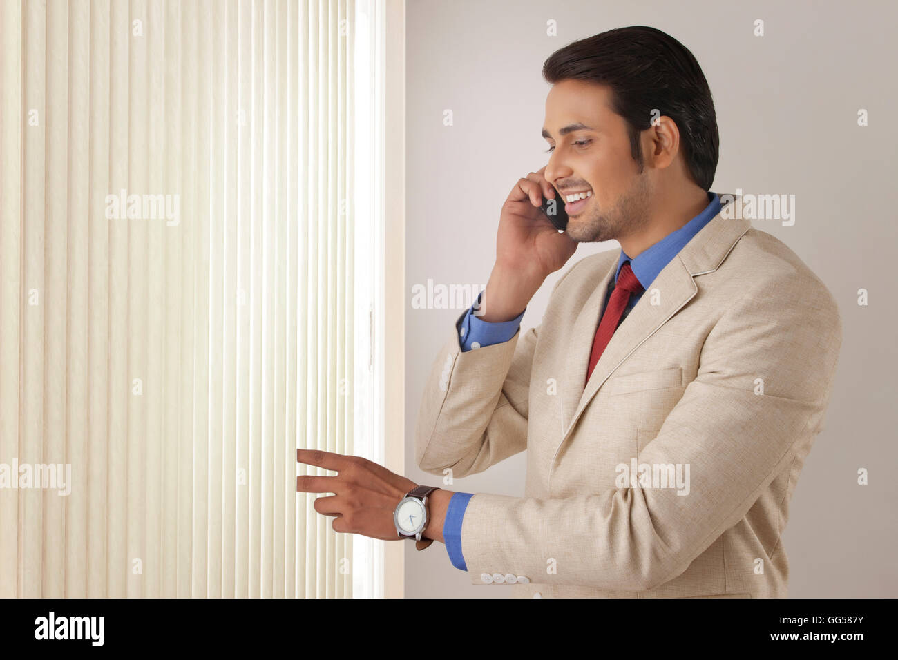 Young businessman on call while looking through window blinds - Stock Image