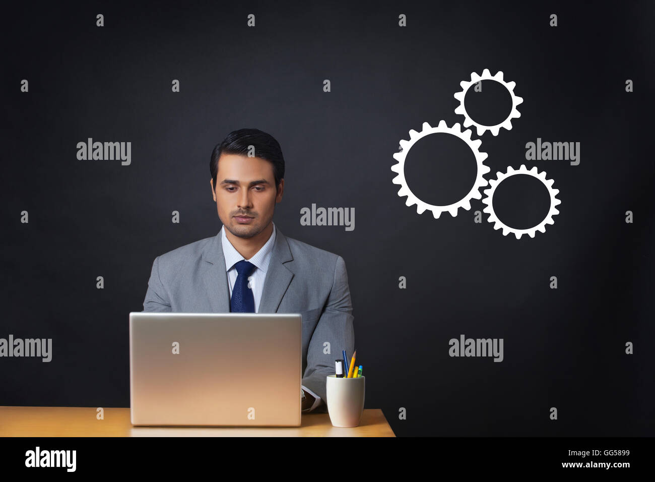Digitally generated image of businessman using laptop at office desk with gears - Stock Image