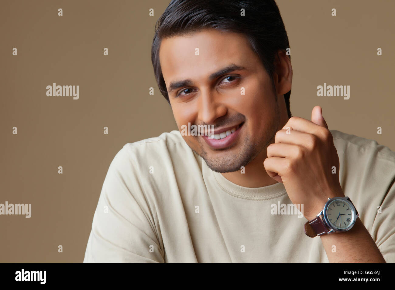 Portrait of Indian man smiling over colored background - Stock Image