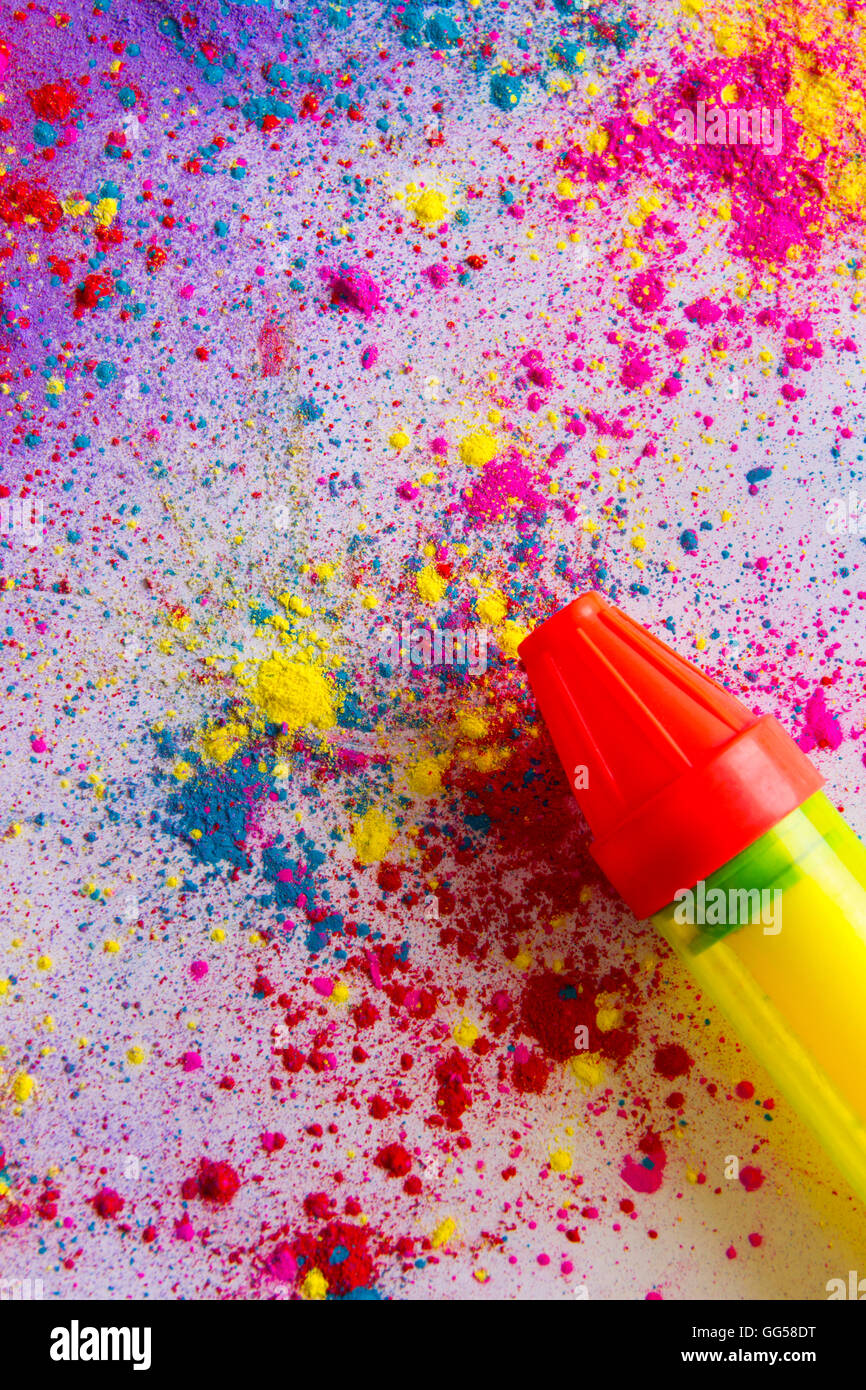 Squirt gun on colorful powder paint spread over white background - Stock Image