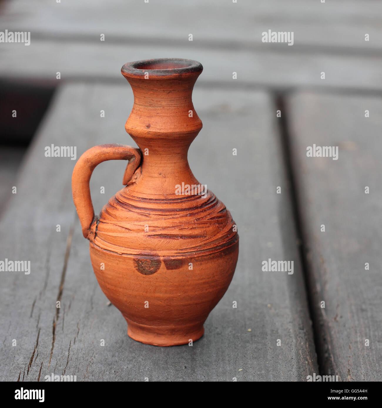 Storage for liquids - Old Vintage jug ewer on darkly brown wooden background. Stock Photo
