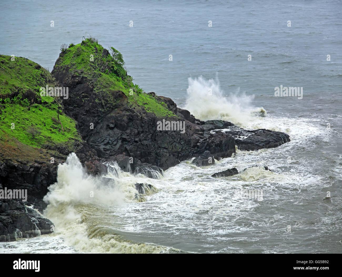 Ocean waves breaking and splashing on rocky cliff during monsoon season in Goa, India. - Stock Image