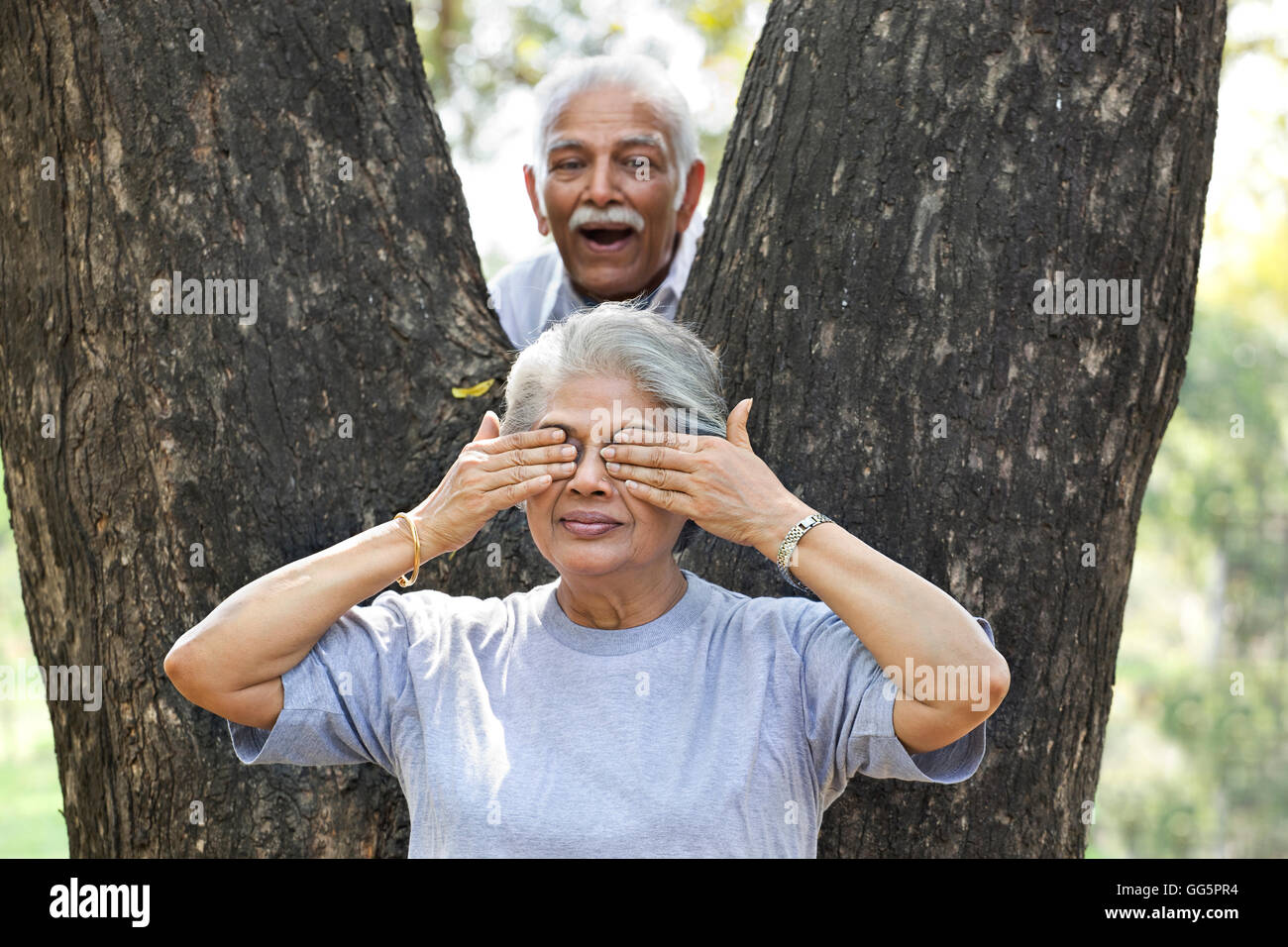 Senior mature man and woman playing hide and seek at park - Stock Image