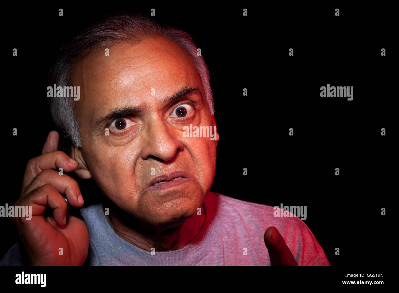 Close Up Of And Angry Old Man Talking On Mobile Phone Stock Photo