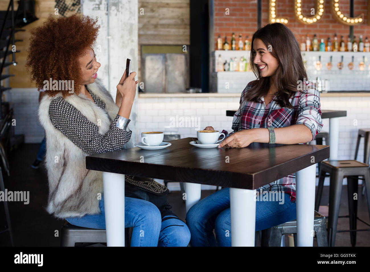 Young woman taking a picture of her friend with smartphone at cafe Stock Photo
