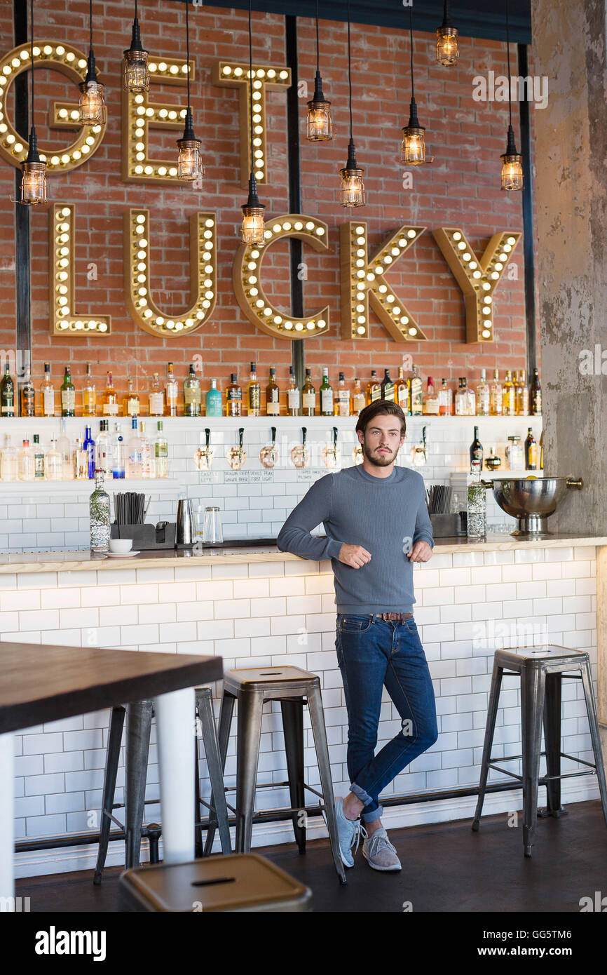 Young man standing at bar counter - Stock Image