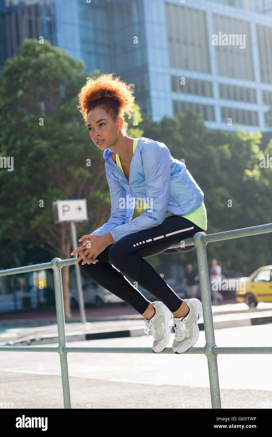 Young female athlete taking a break during exercise by railings on street - Stock Image