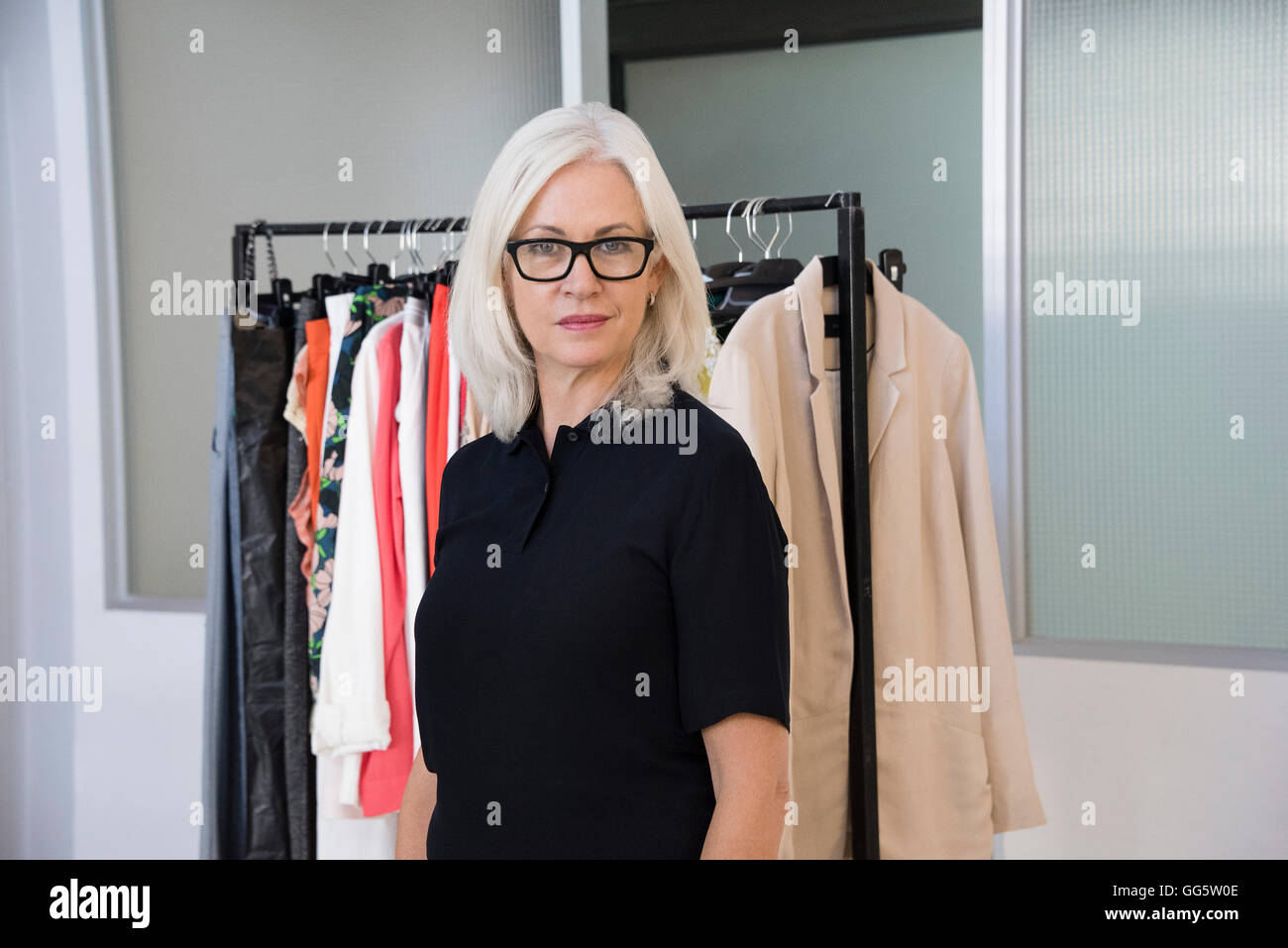 Dress designer standing in her office - Stock Image