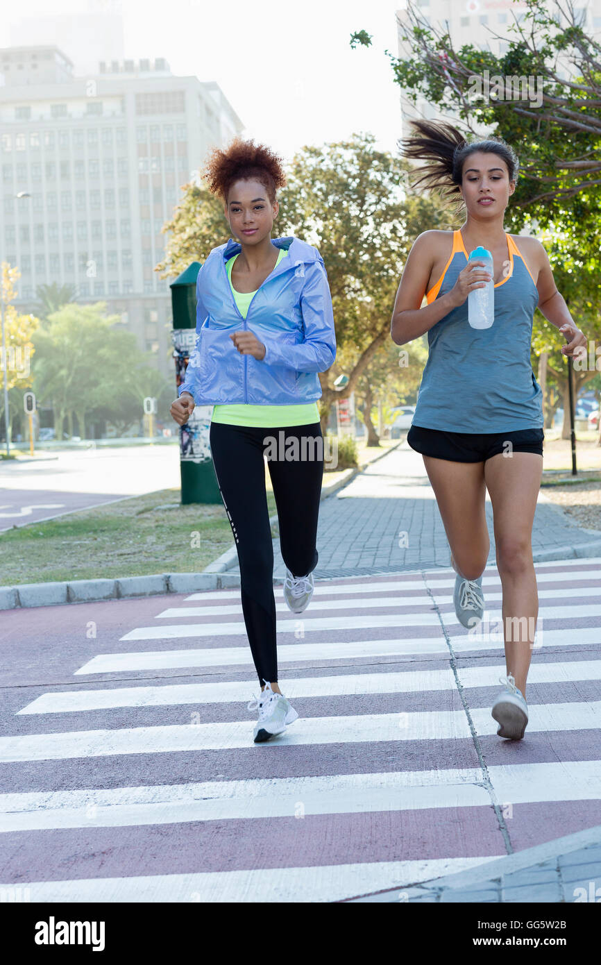 Young female athletes running in a park - Stock Image