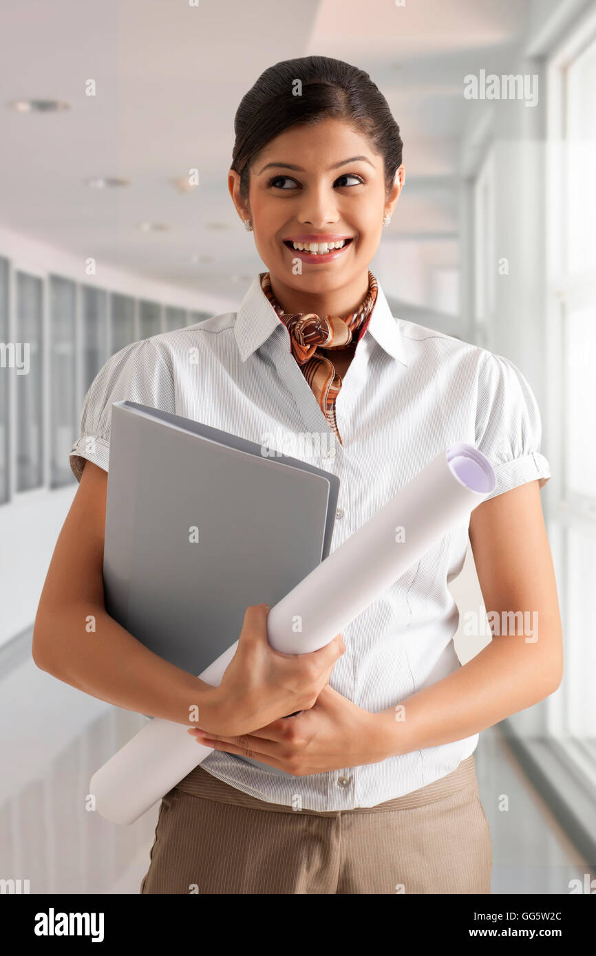 Young businesswoman smiling confidently while holding documents Stock Photo