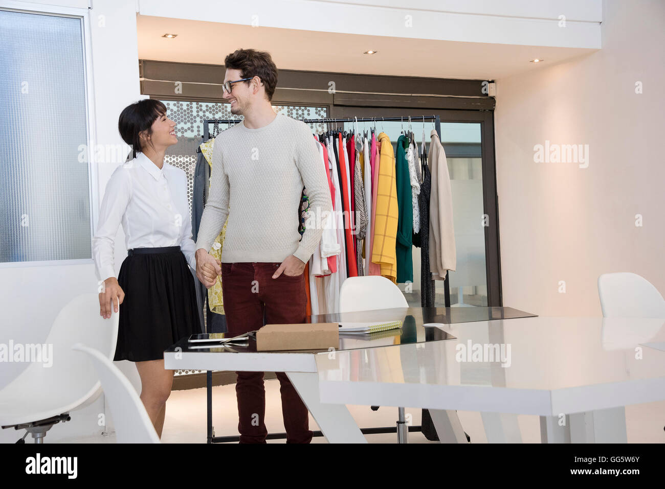 Design professionals smiling in clothing design studio - Stock Image