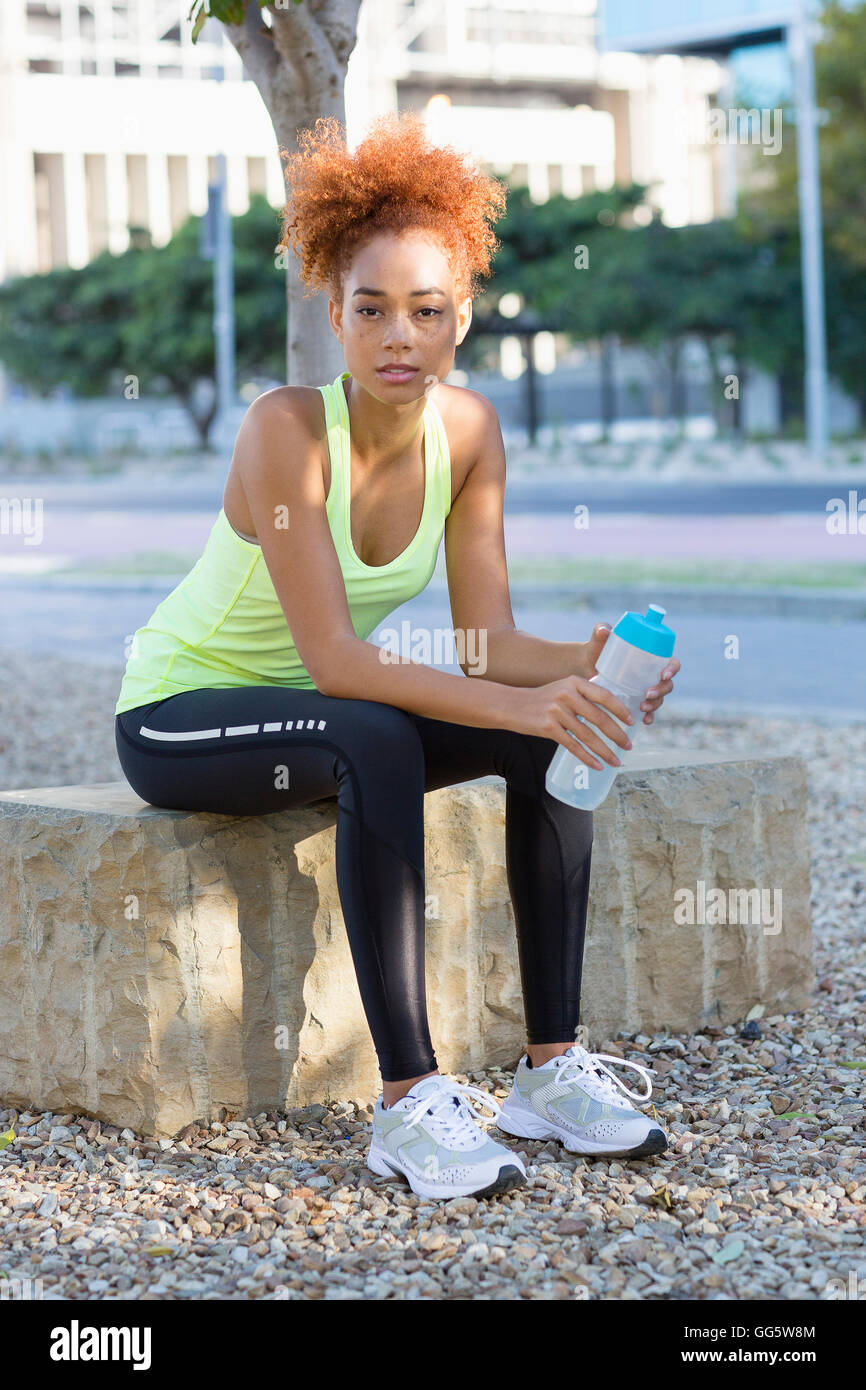 Young female athlete taking a break during exercise in city park - Stock Image