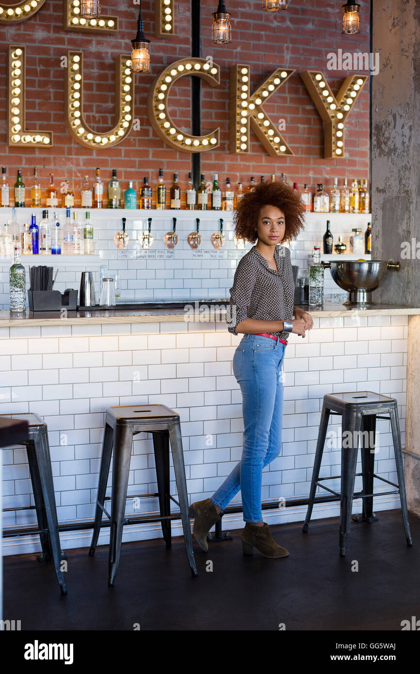 Portrait of a young woman standing at bar counter - Stock Image