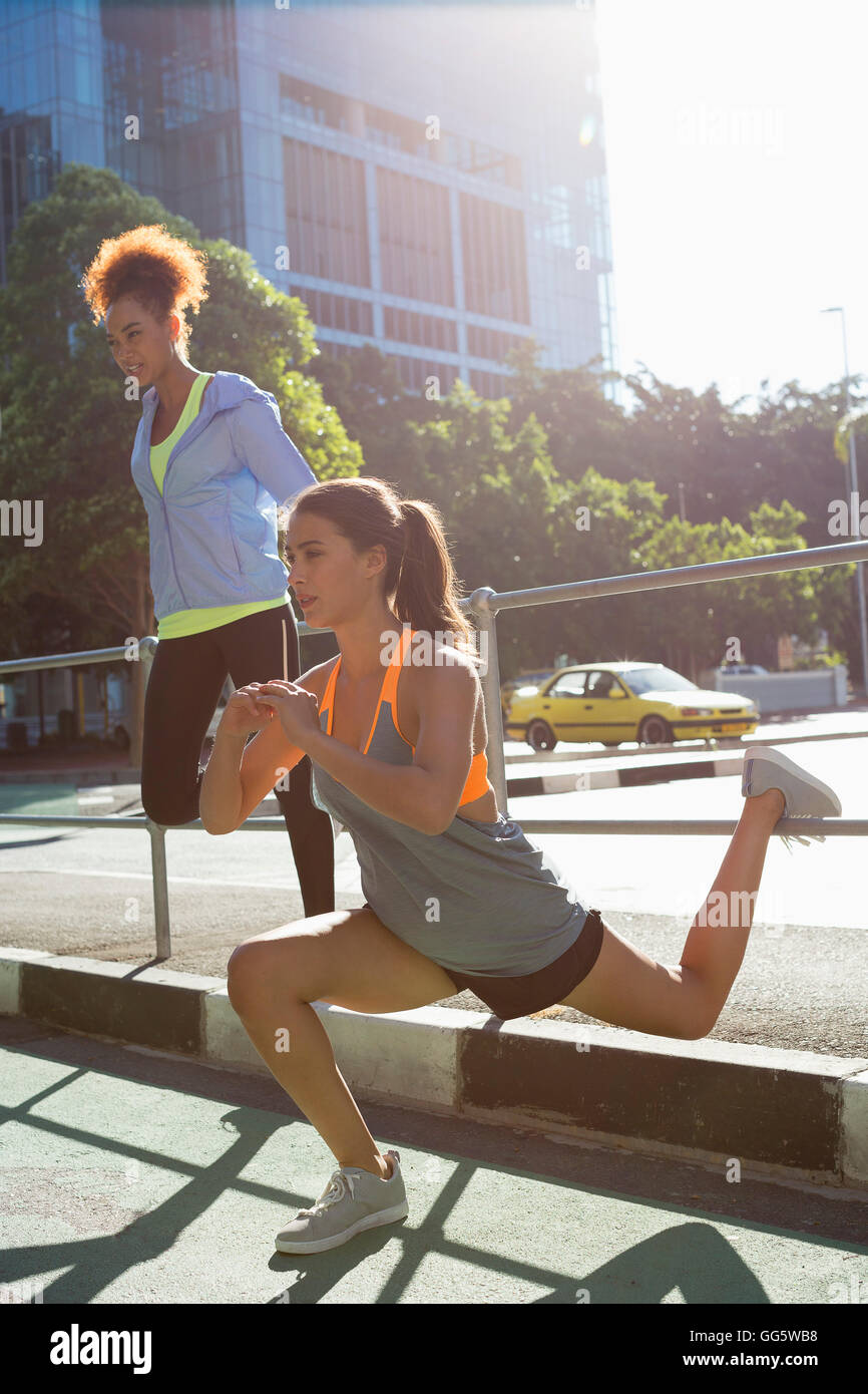 Young female athletes doing stretching exercise by railings on street - Stock Image