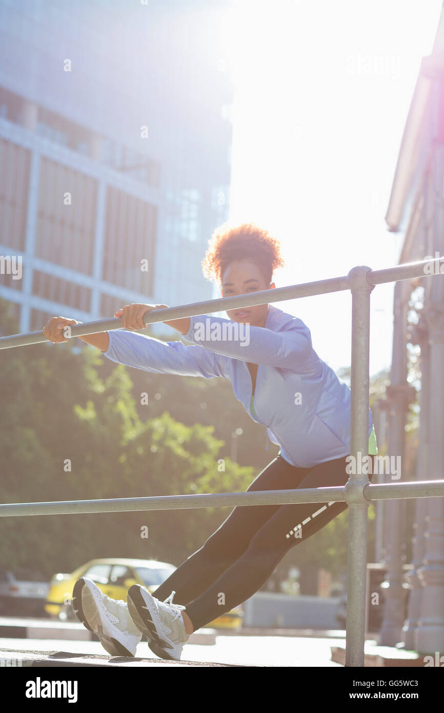 Young female athlete doing stretching exercise by railings on street - Stock Image