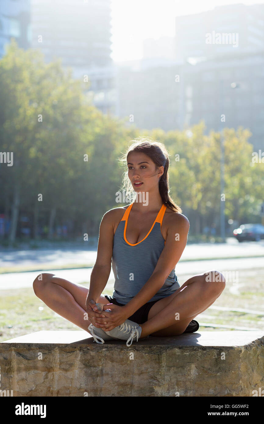 Young female athlete doing exercise in city park Stock Photo