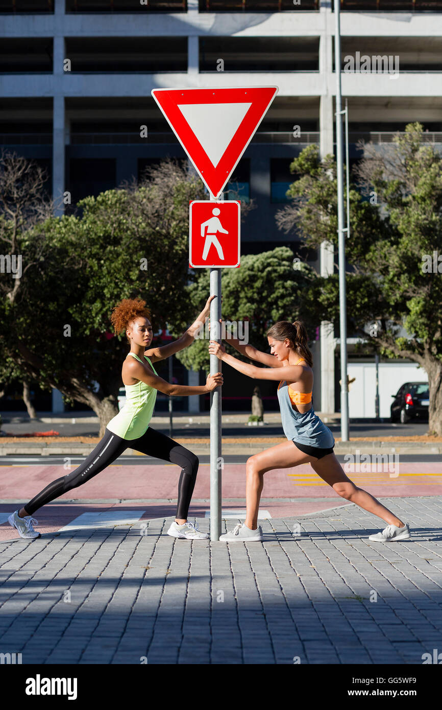Young female athletes doing stretching exercise by pole on street - Stock Image