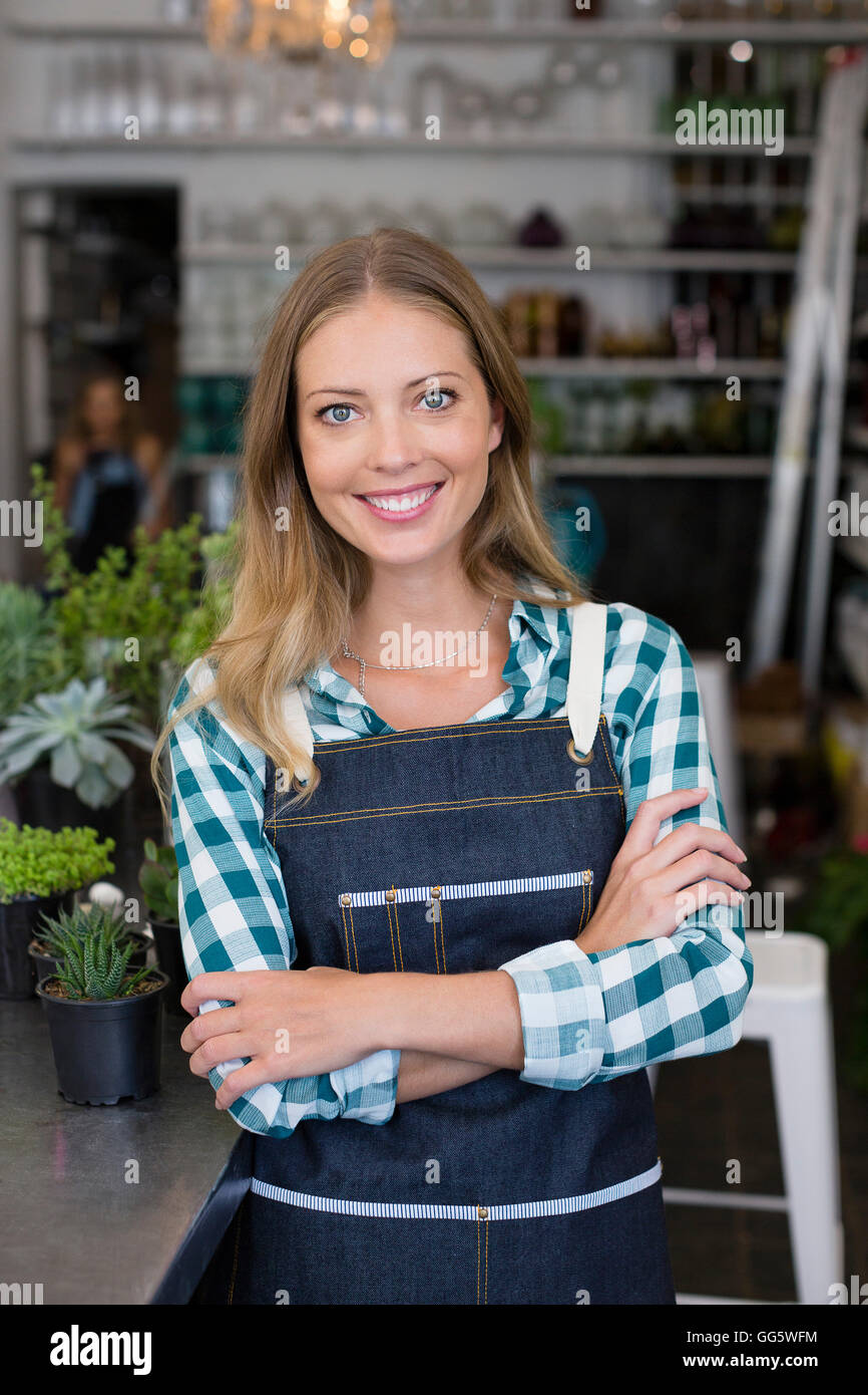 Happy florist standing with her arms crossed - Stock Image
