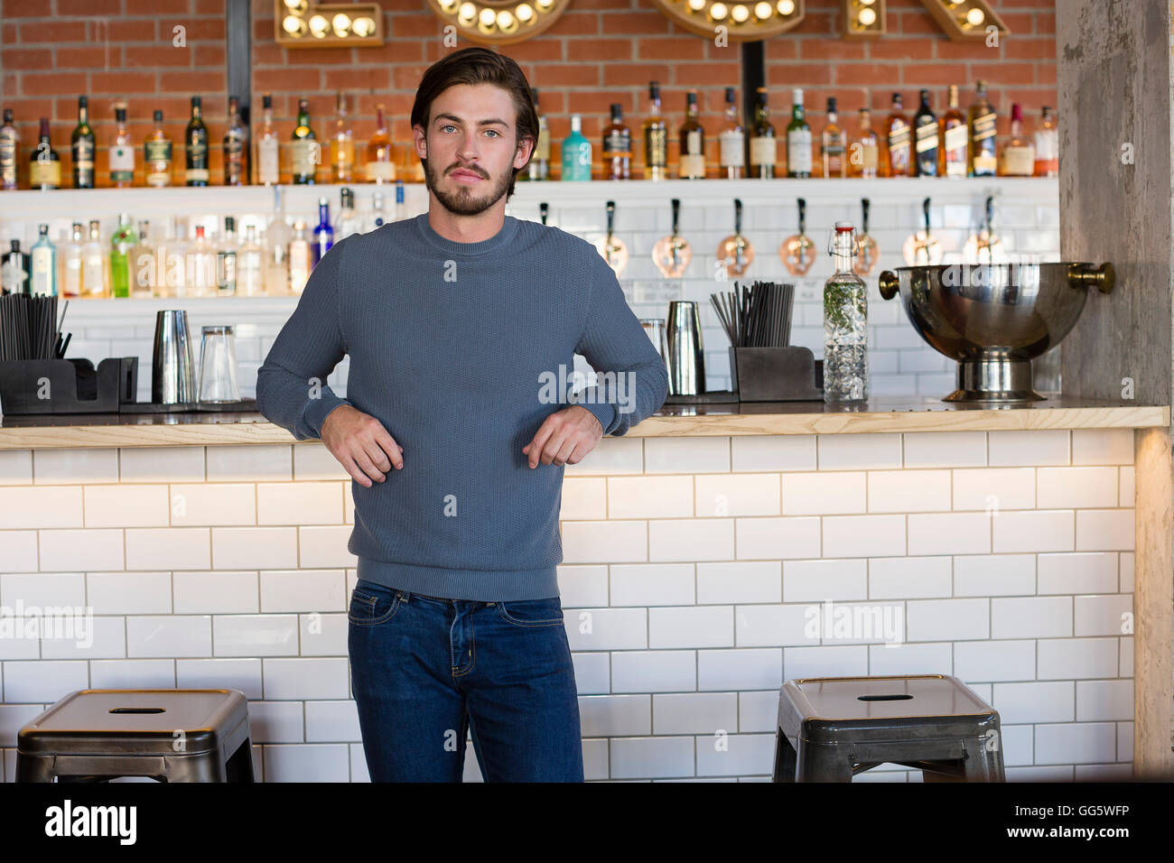Portrait of a young man standing at bar counter - Stock Image