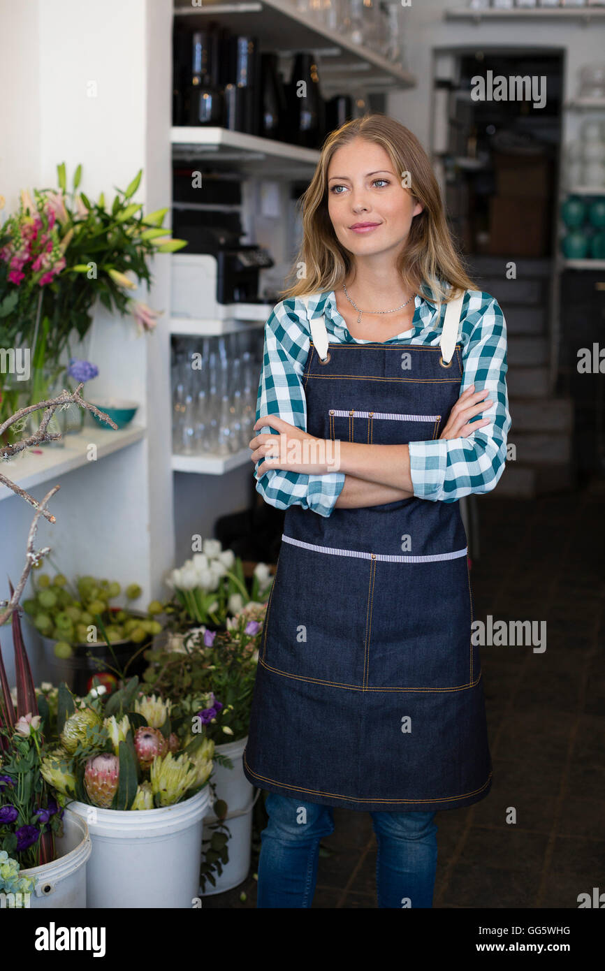 Florist standing with her arms crossed in her shop - Stock Image