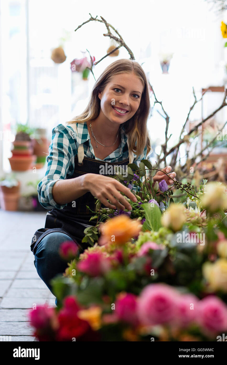 Portrait of a florist smiling at her shop - Stock Image
