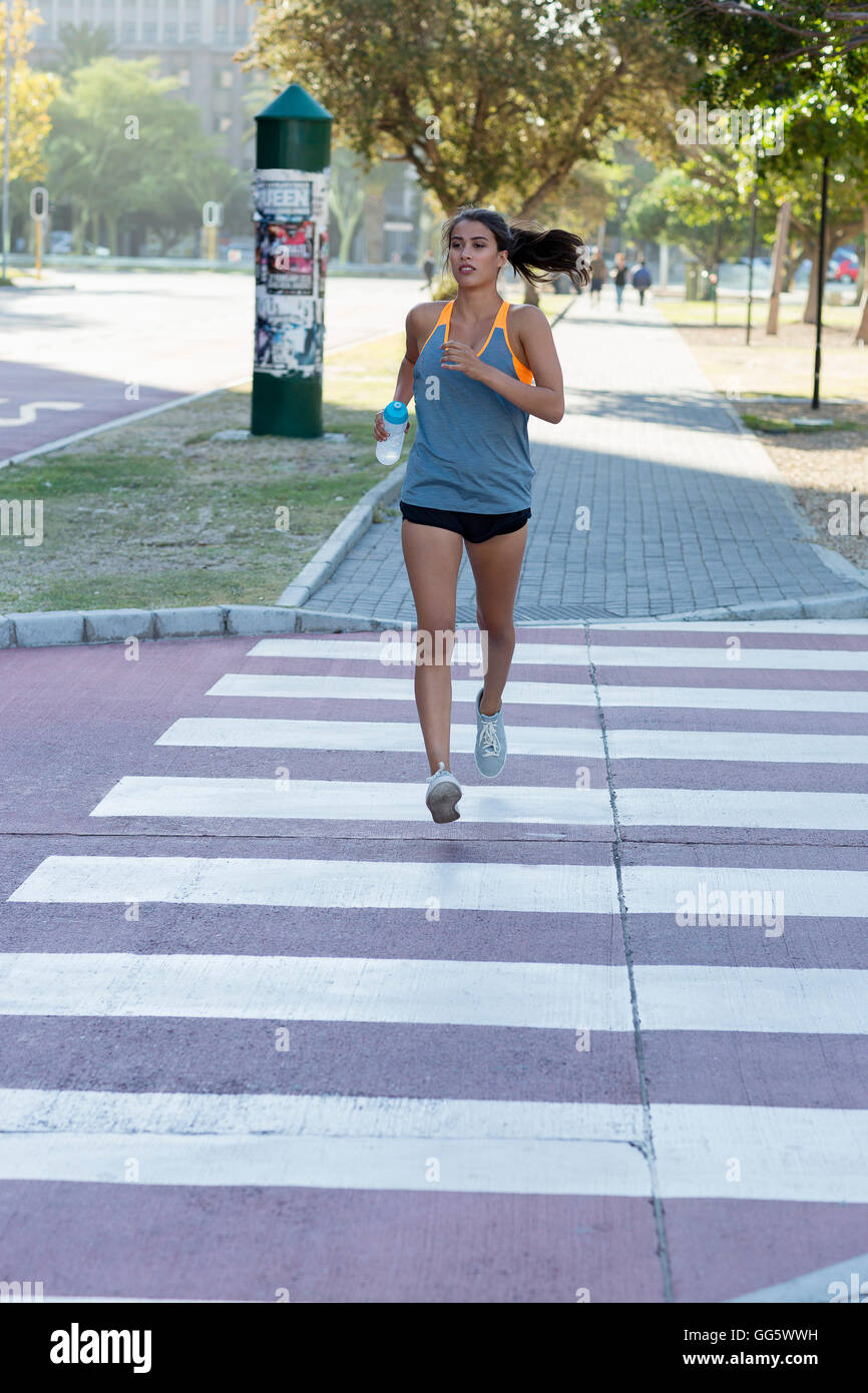 Young female athlete running in a park - Stock Image
