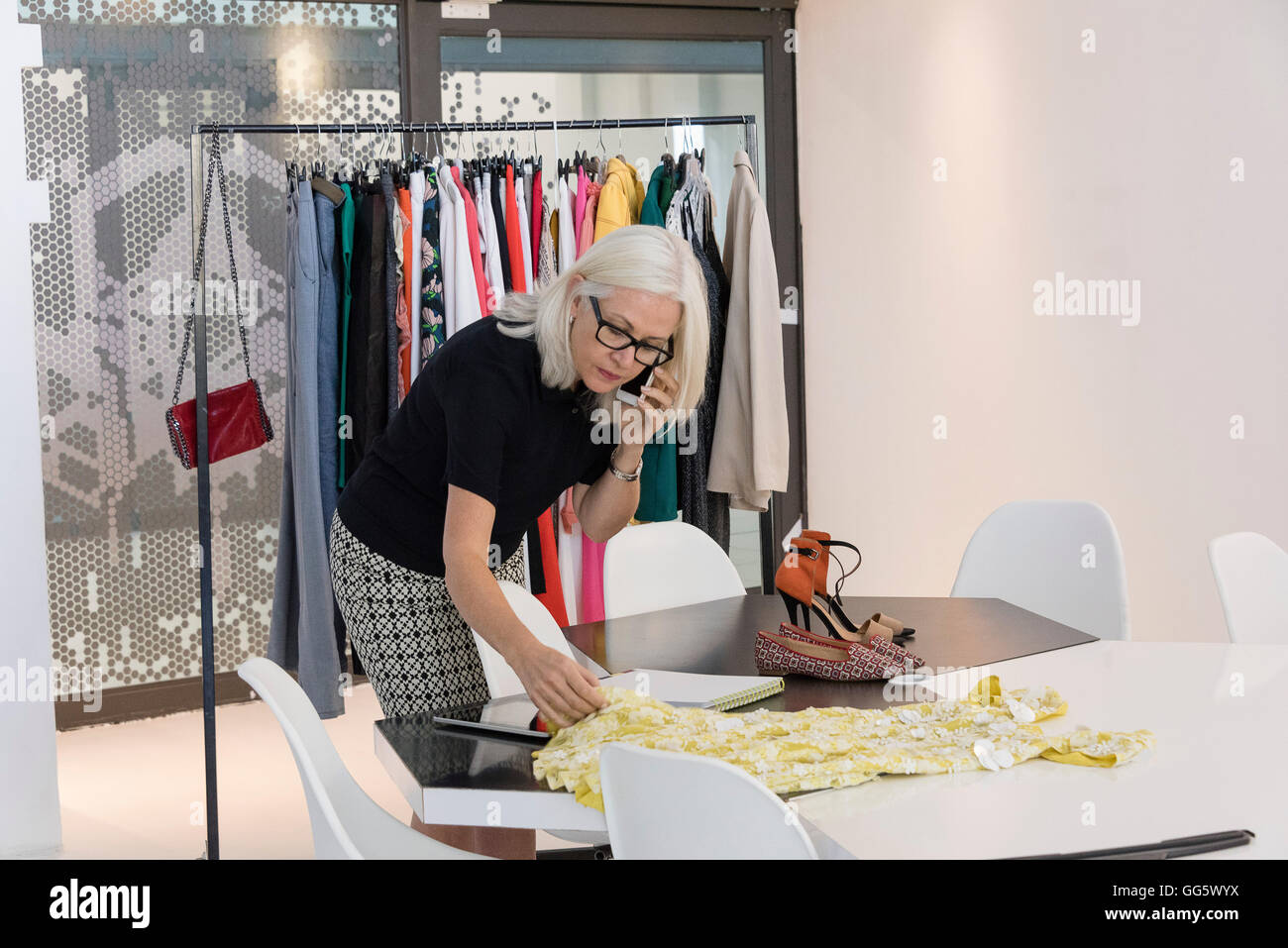 Fashion designer working in her studio - Stock Image