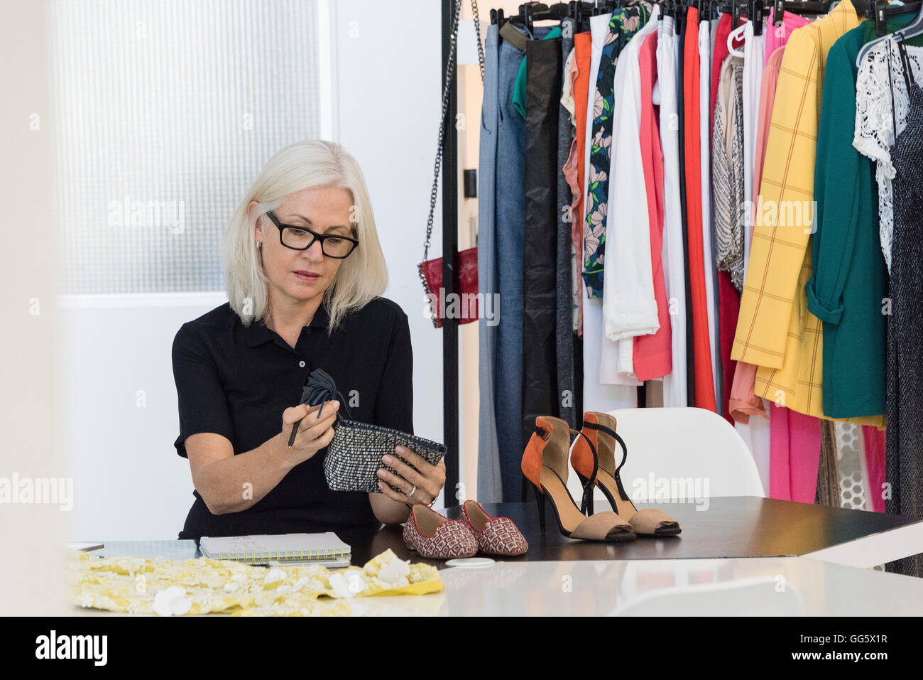 Female dress designer working in her shop - Stock Image