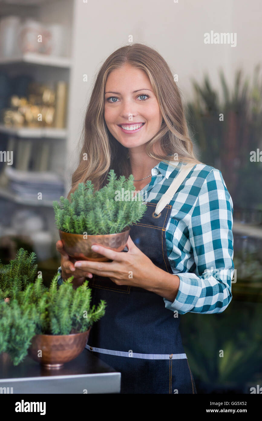 Portrait of a happy woman holding a potted plant - Stock Image