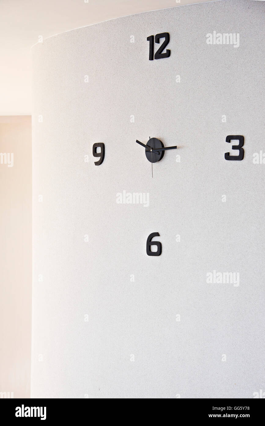Close-up of wall clock against white wall - Stock Image