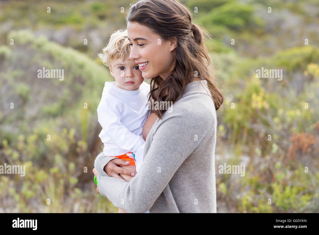 Happy beautiful woman carrying her baby - Stock Image