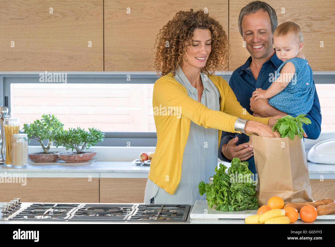 Family taking out food from paper bag in the kitchen - Stock Image