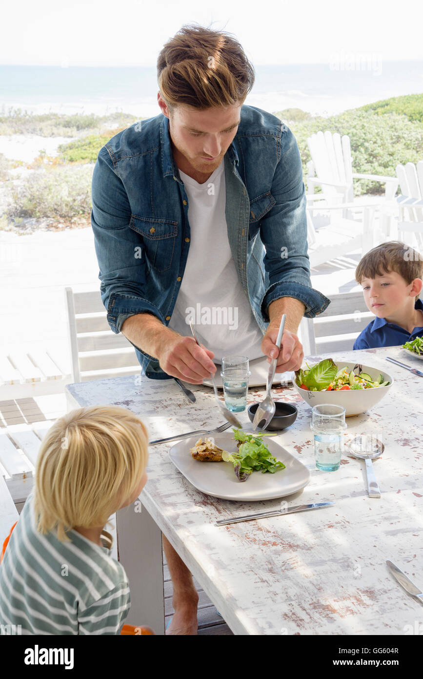 Father serving food to children on table Stock Photo