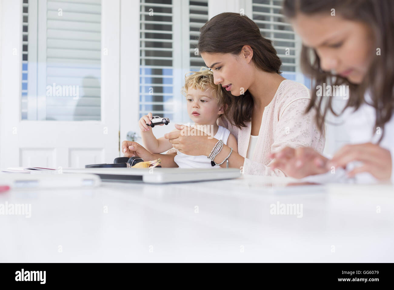 Mother playing with children at home - Stock Image