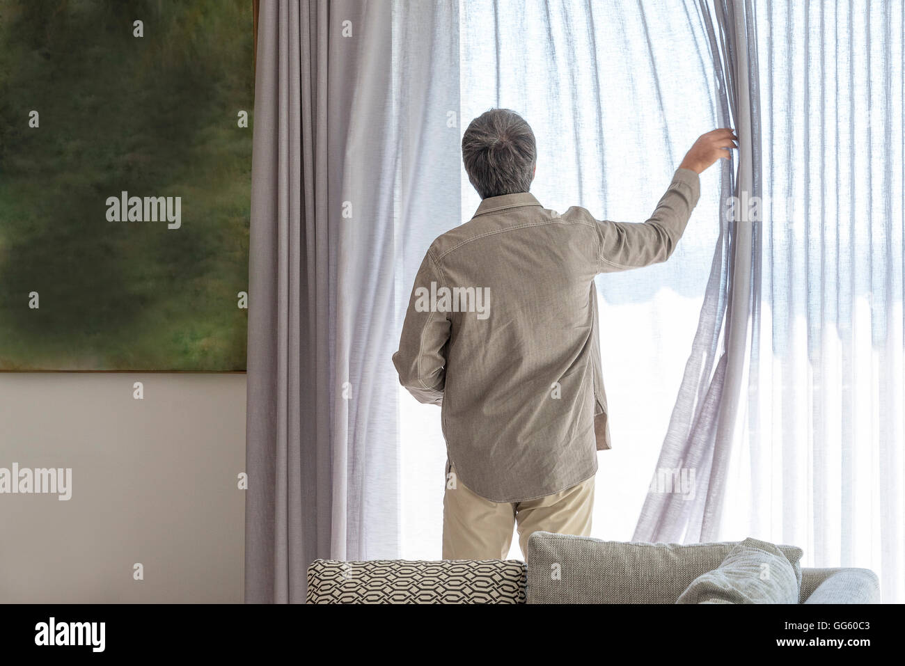 Rear view of a man holding curtain on window - Stock Image