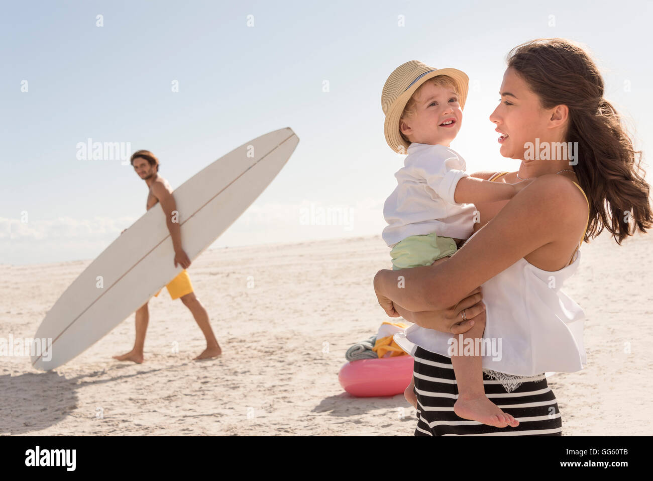 Happy young family enjoying on beach - Stock Image