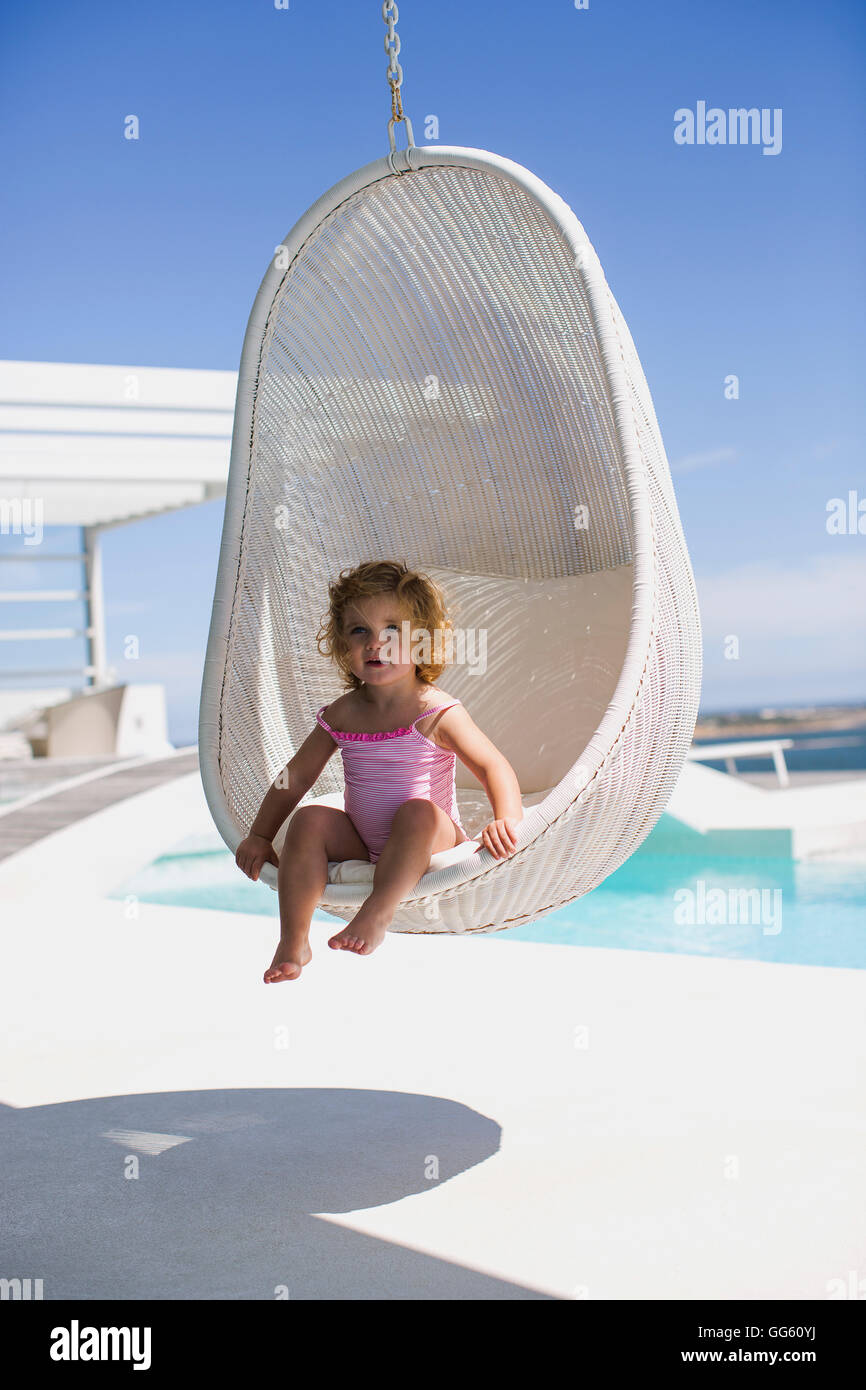 Baby girl sitting in a wicker swing - Stock Image