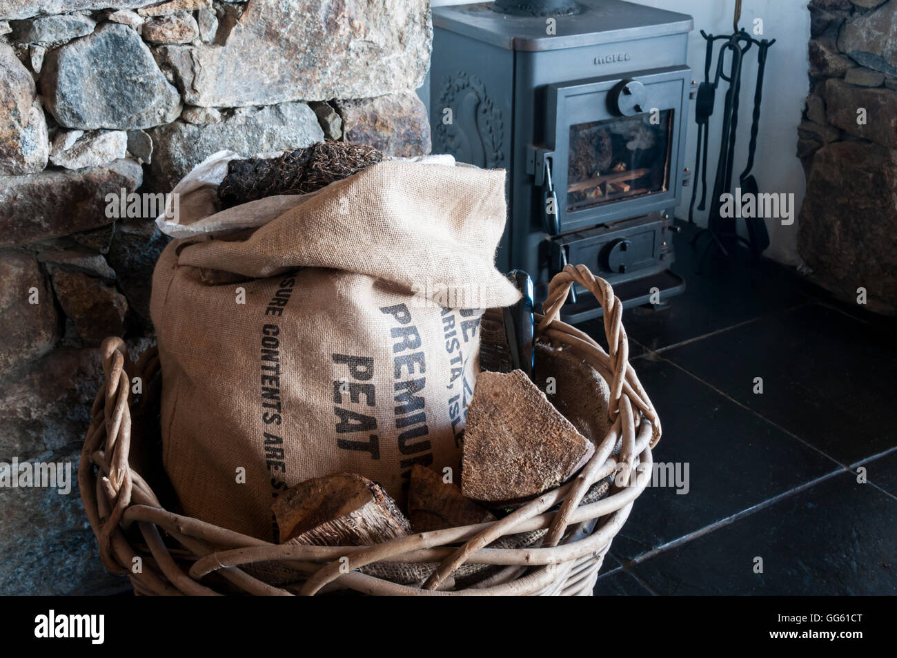 Sack of peat in a house in Outer Hebrides for use as fuel in Morsø wood-burning stove in background. - Stock Image