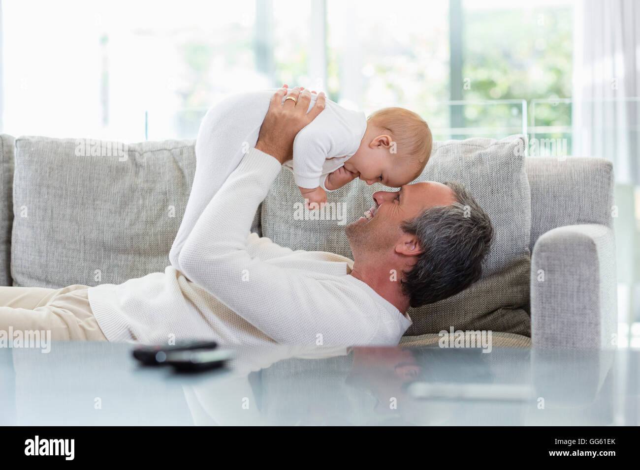Happy father playing with his cute baby daughter at home - Stock Image