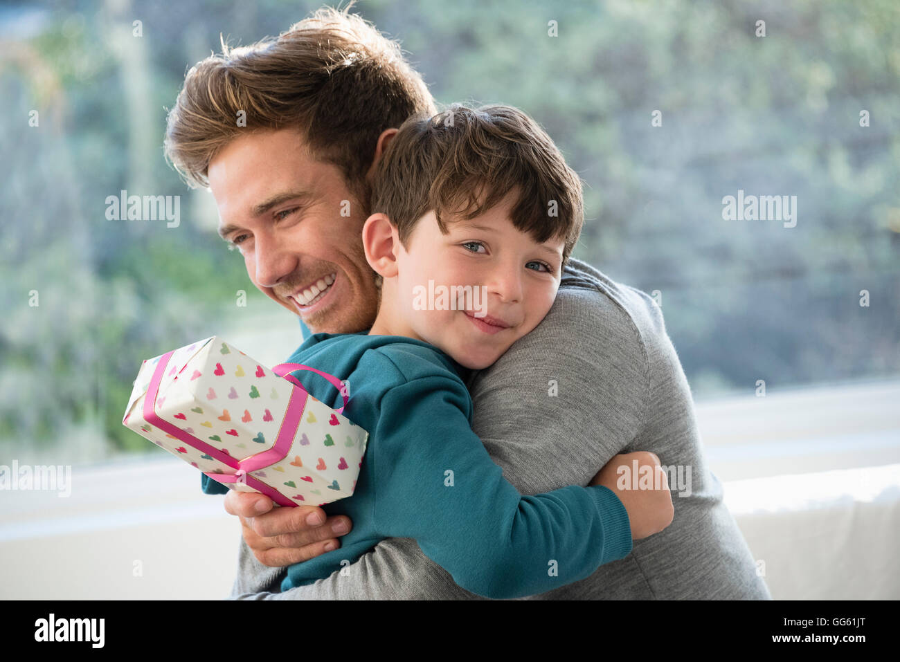 Loving Father And Son Hugging With Birthday Gift