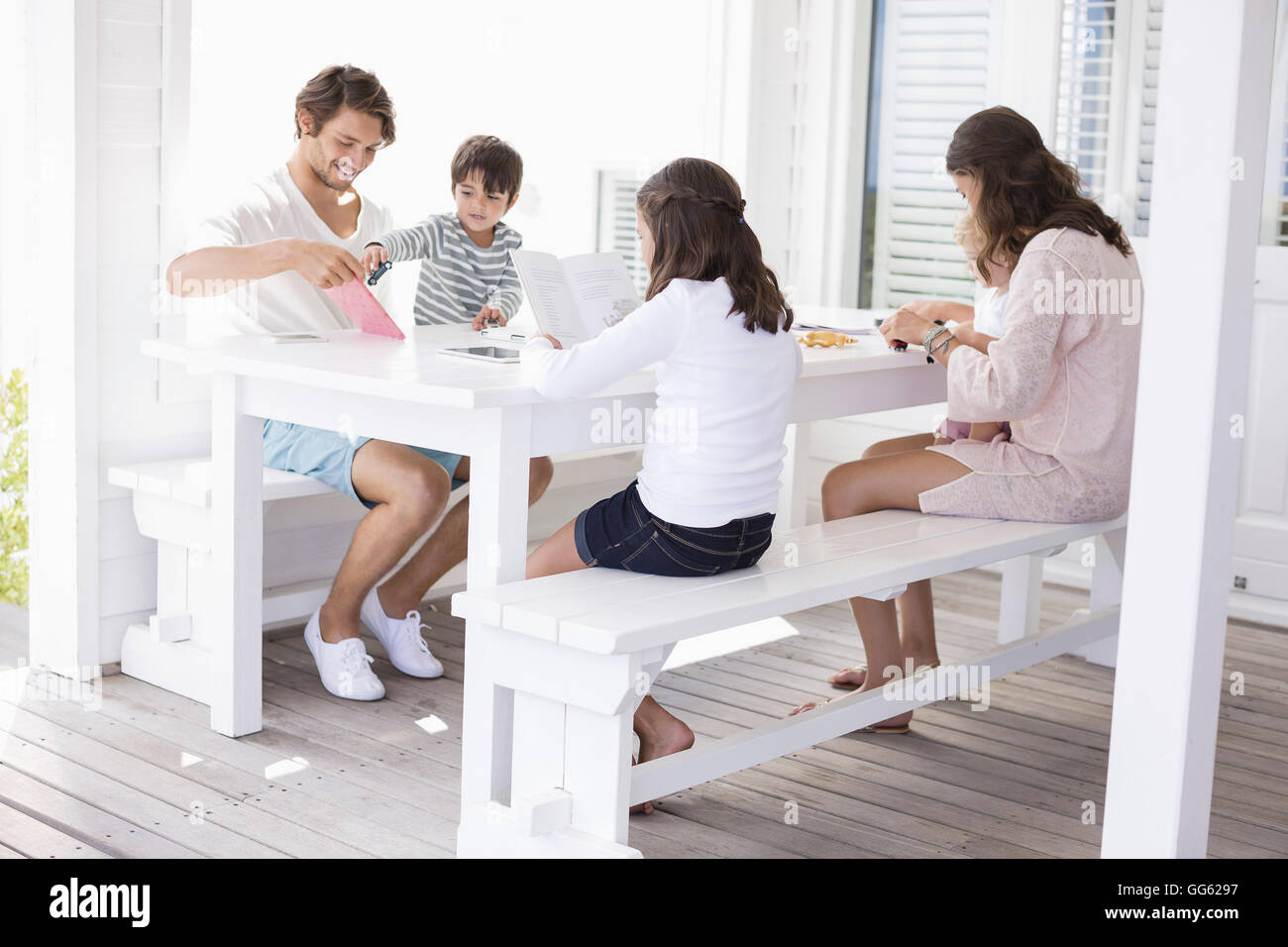 Happy young family sitting together at home - Stock Image