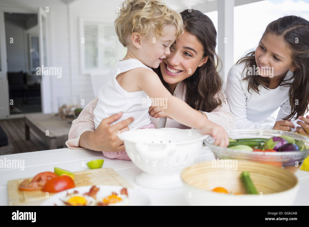Happy young family preparing vegetables at home Stock Photo