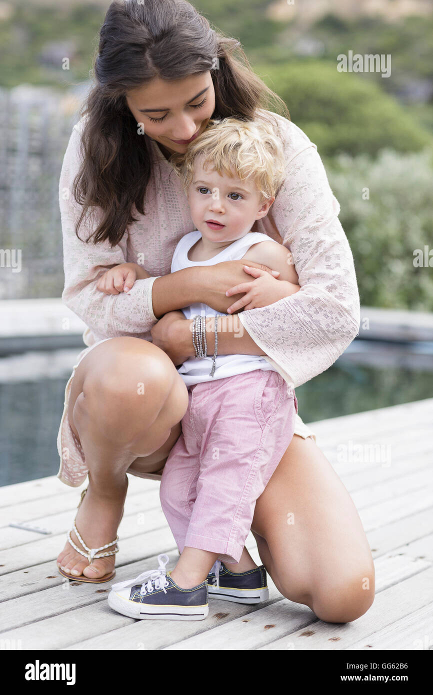 Happy mother playing with son at poolside - Stock Image