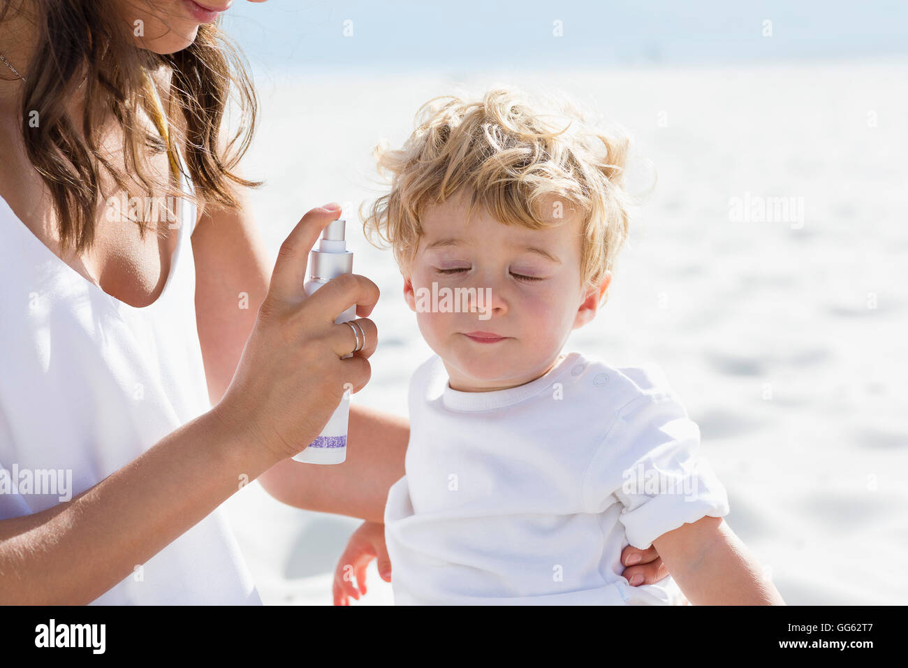 Woman holding a bottle of suntan lotion with her son - Stock Image